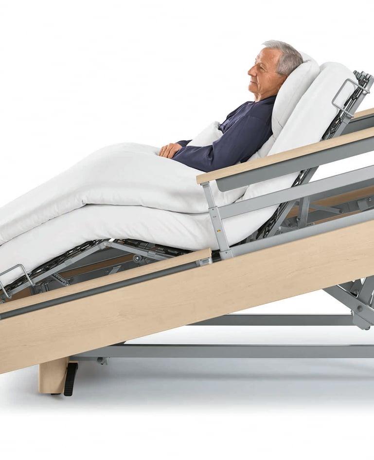 Nahaufnahme eines Mannes in einem Niedrigpflegebett. Rahmen des Betts schräg aufgerichtet, Matratze formt gemütliche Sitzposition