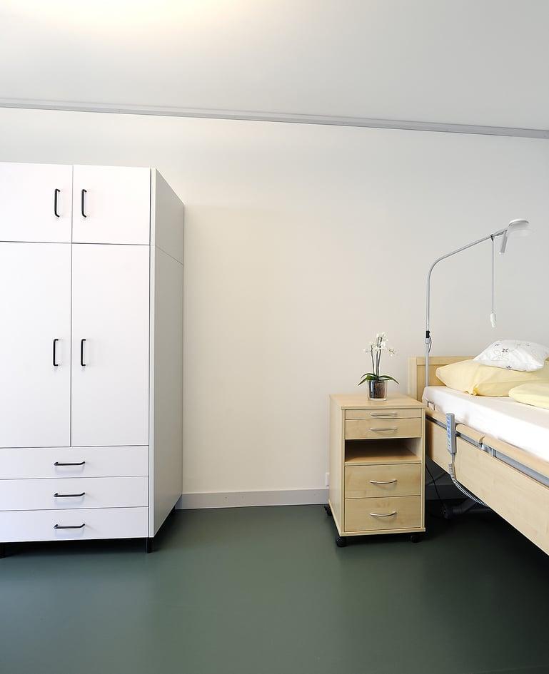 Bewohnerzimmer mit Frontalansicht auf weissen Kleiderschrank und Pflegebett mit passendem Nachttisch