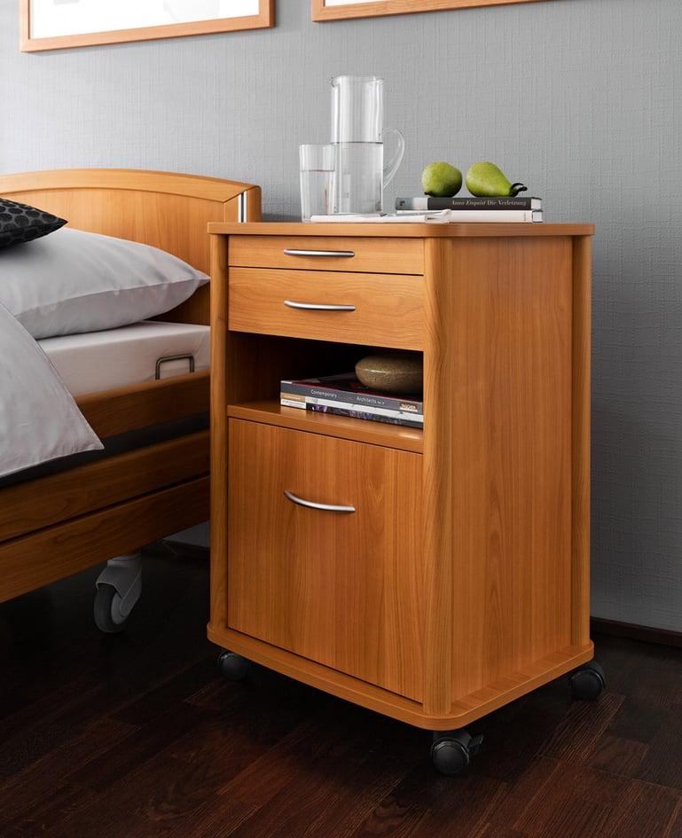 Mobiler Nachttisch aus Kirsche passend zum Niedrigpflegebett, darauf befinden sich ein Krug und ein Glas Wasser, Bücher und Früchte