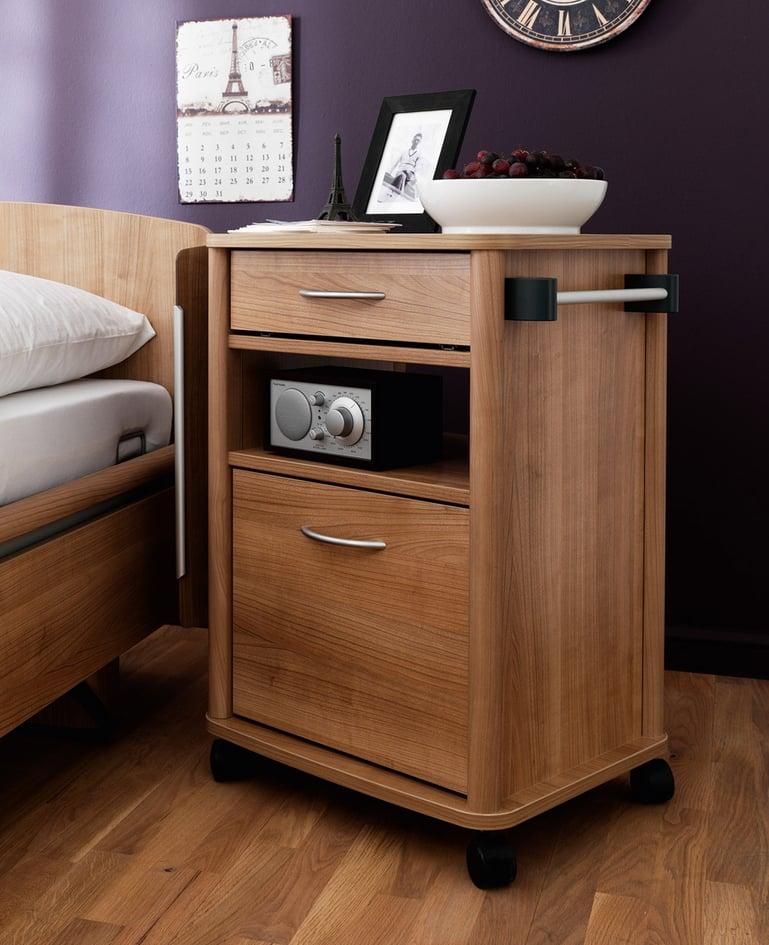 Mobiler Nachttisch aus dunklem Holz mit zwei Schubladen und Radio auf Zwischenablage. Das Möbel ist passend zum Niedrigpflegebett