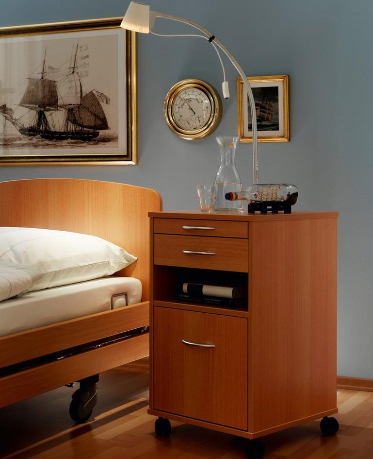 Funktionaler fahrbarer Nachttisch aus dunklem Holz mit Schubladen und offenem Staufach. Wohnliche Atmosphäre.