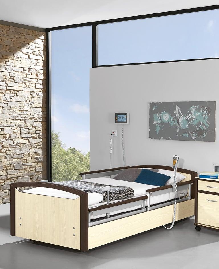 Niedrigpflegebett sentida 7-i mit technischer Ausstattung. Touchpanel an der Wand hinter dem Bett