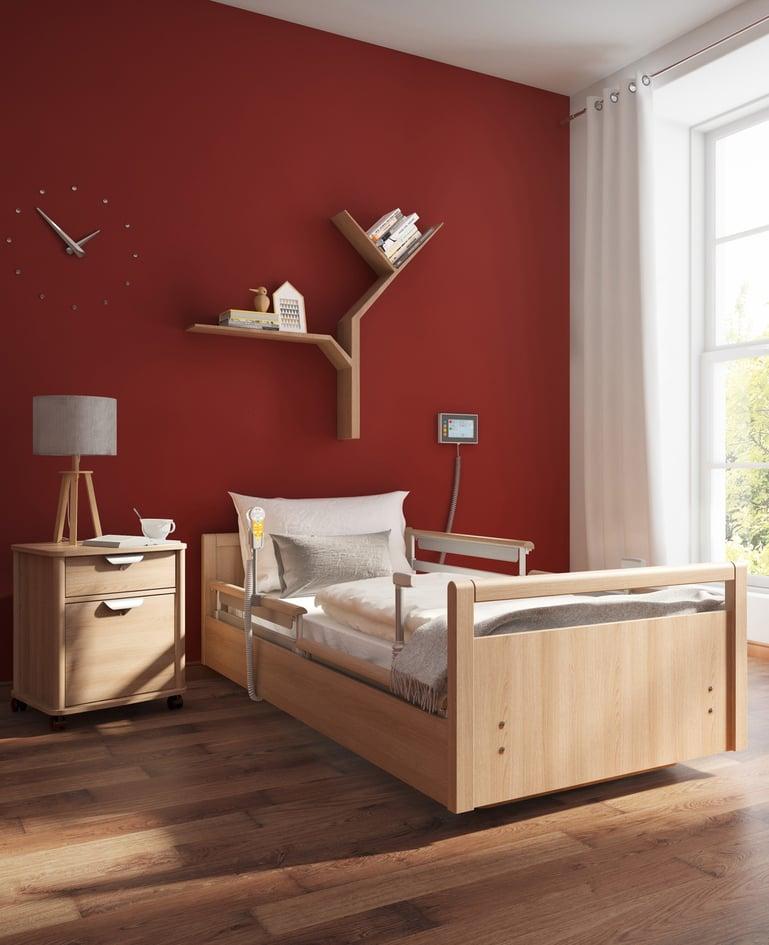 Niedrigpflegebett sentida 7-i in wohnlichem Zimmer mit technischer Ausstattung. Touchpanel an der Wand hinter dem Bett