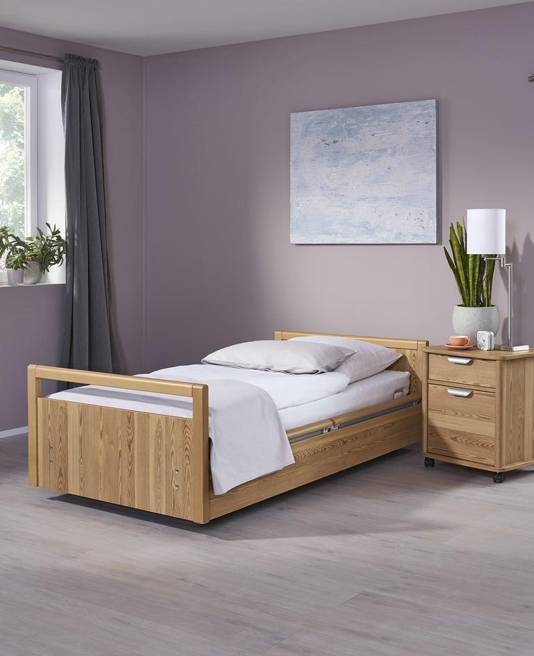 Mobiles sentida Niedrigpflegebett aus hellem Holz mit passendem Nachttisch in einem Raum mit Grautönen
