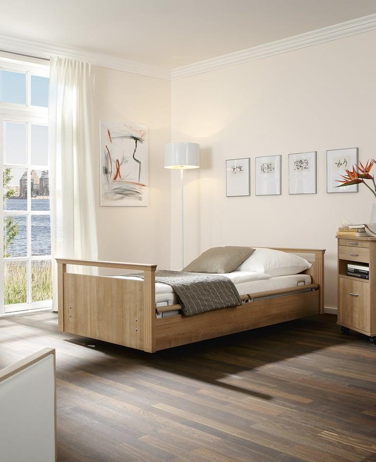 Mobiles sentida Niedrigpflegebett mit passendem Nachttisch in einem lichtdurchfluteten, hellen Raum