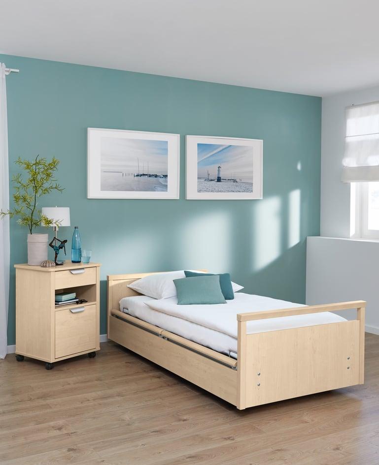 Mobiles sentida Niedrigpflegebett mit passendem Nachttisch in einem lichtdurchfluteten Raum mit Türkistönen