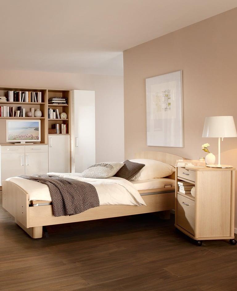 Mobiles sentida Niedrigpflegebett aus hellem Holz mit passendem Mobiliar in wohnlicher Atmosphäre