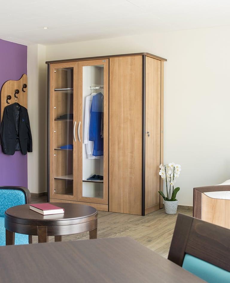 Kleiderschranksystem mit zwei von drei Türen aus Glas und Garderobe links davon. Sitzecke angeschnitten im Vordergrund