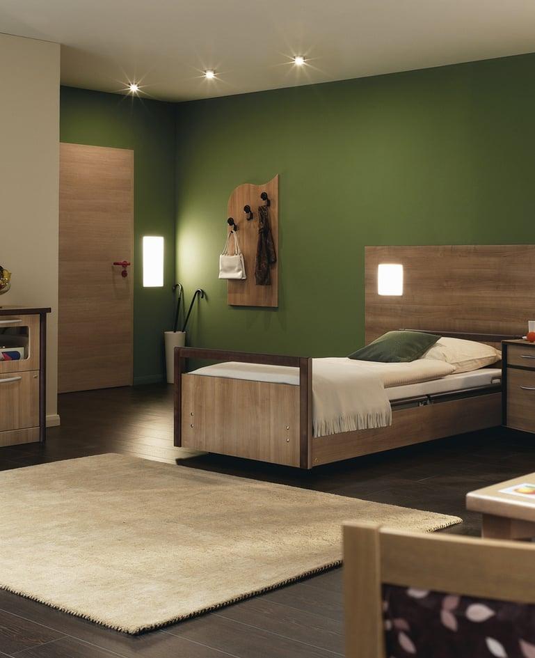 Gemütliches Bewohnerzimmer mit sentida Niedrigpflegebett und stilvoller Einrichtung, künstlich beleuchtet