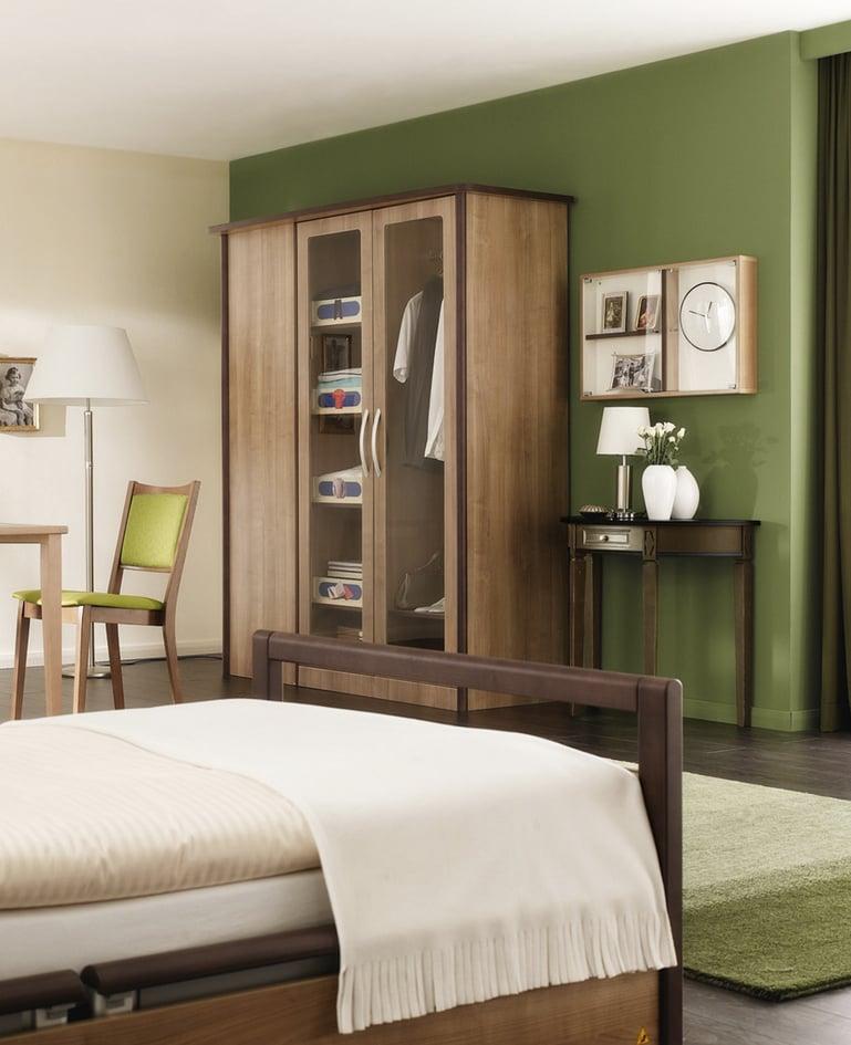 Fussende des sentida Niedrigpflegebetts mit Blick auf Kleiderschranksystem mit Orientierungshilfen, Memory Box und passendem Beistelltisch