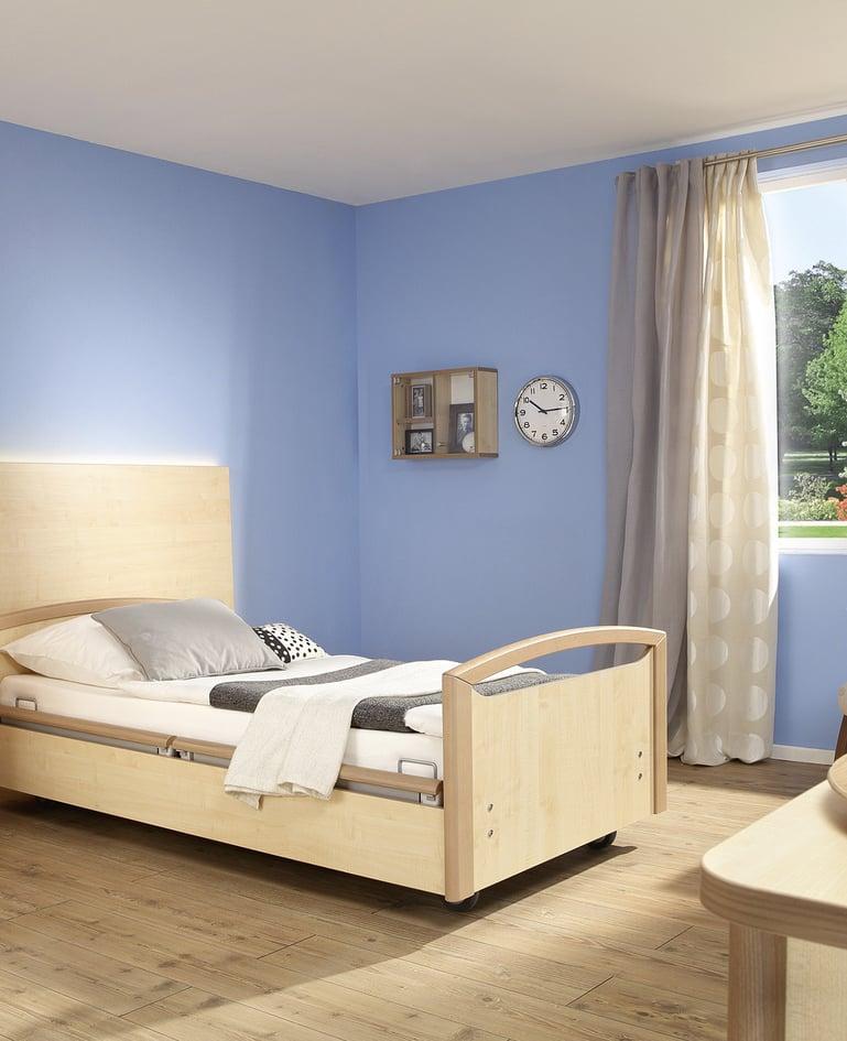 Mobiles sentida Niedrigpflegebett mit passendem Nachttisch in einem Zimmer mit blauen Wänden