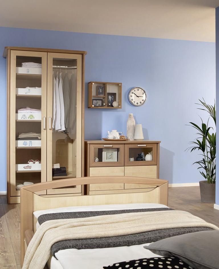 Heller Raum mit sentida Niedrigpflegebett, Kleiderschrank sowie Kommode mit Glasfronten und Memory Box und Uhr an der Wand.