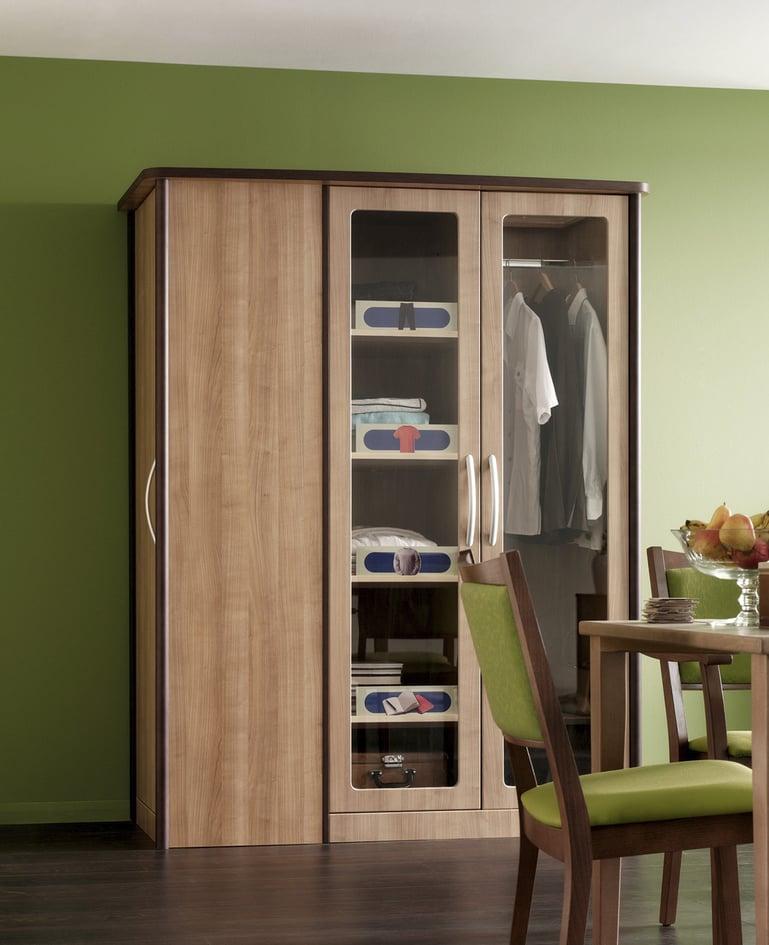 Kombinationsschrank mit zwei von drei Türen aus Glas, darin Zubehör für Kleiderschrank als Orientierungshilfen. Im Bild angeschnitten ein Tisch mit zwei Stühlen.