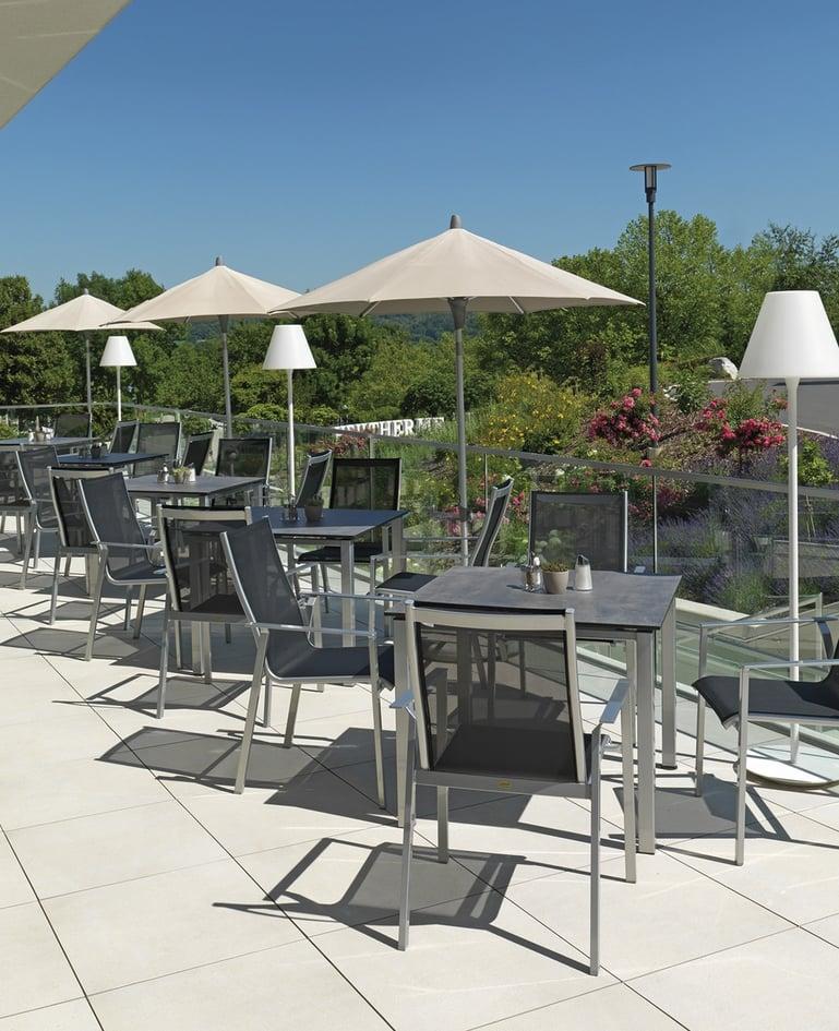 Tische aus Stahlrohr mit dunkler Tischfläche und Stühle aus Stahlrohr mit dunkelgrauer Bespannung in Aussensitzbereich