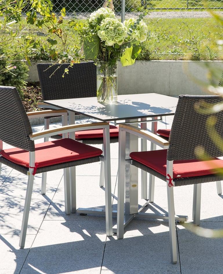 Vier Stühle mit Polster um Tisch mit Blumenvase gruppiert auf einer sonnigen Terrasse