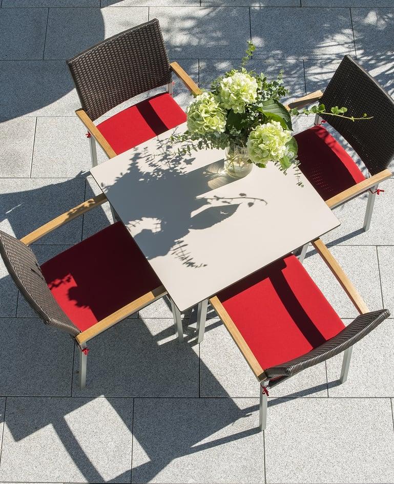 Vogelperspektive auf Tisch und passende Rattan-Stühle aus Stahlrohr auf sonniger Terrasse. Blumenstrauss auf dem Tisch