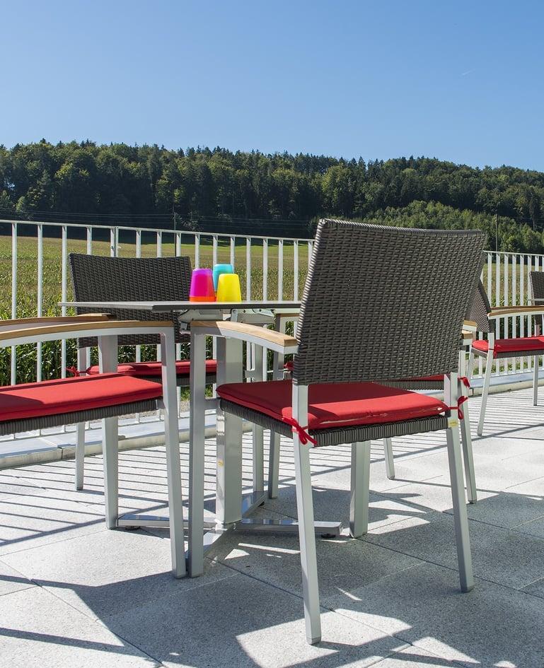 Seitenansicht von Tisch und passenden Rattan-Stühle aus Stahlrohr auf sonniger Terrasse. Bunte Plastikbecher auf dem Tisch