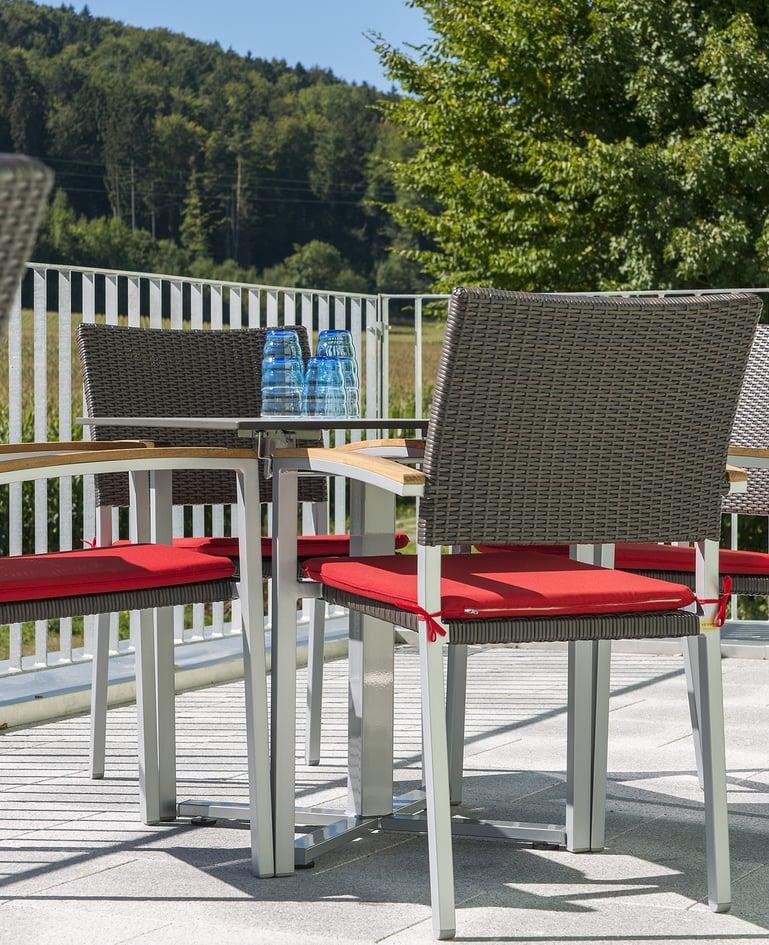 Seitenansicht von Tisch und passenden Rattan-Stühle aus Stahlrohr auf sonniger Terrasse. Wassergläser auf dem Tisch