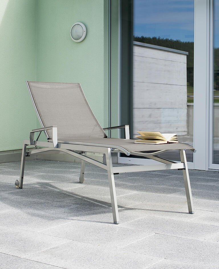 Liegestuhl auf Terrasse, darauf ein geöffnetes Buch