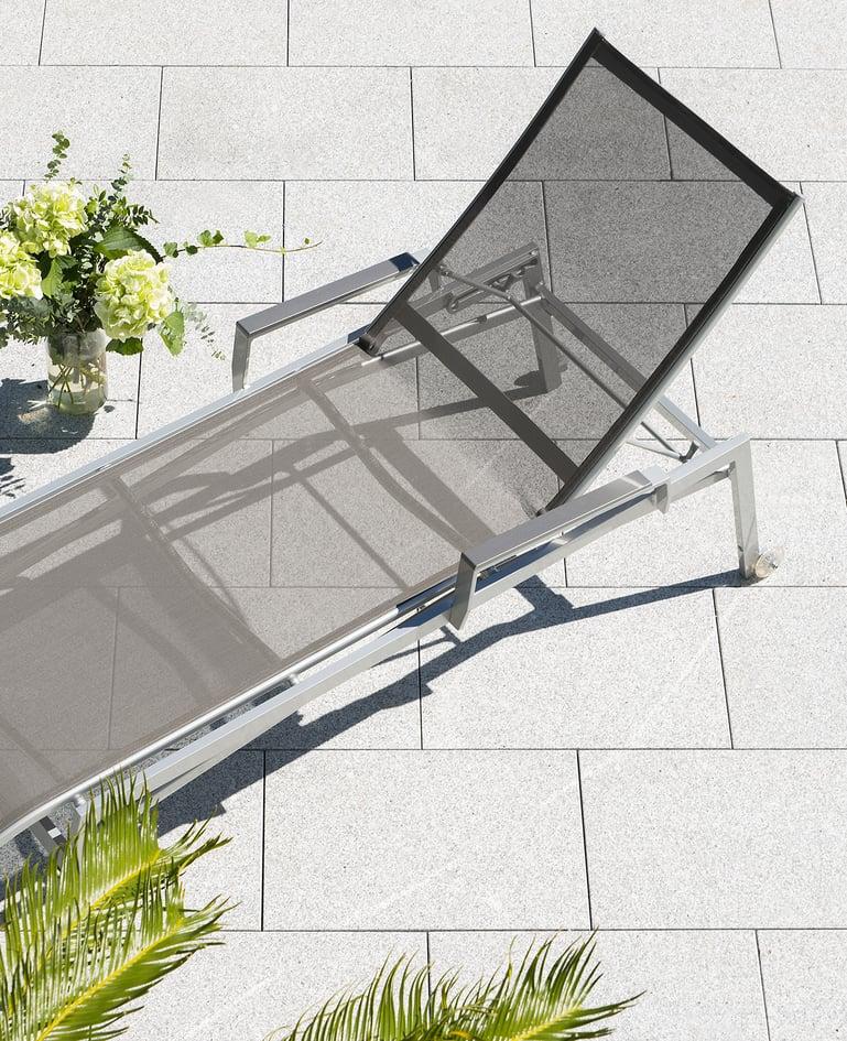 Vogelperspektive auf Stapelliege mit Rollen und grauer Bespannung auf sonniger Terrasse. Blumenstrauss neben der Liege