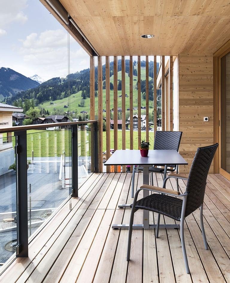 Tisch mit zwei passenden Stühlen auf einem Balkon mit Blick in die Bergwelt