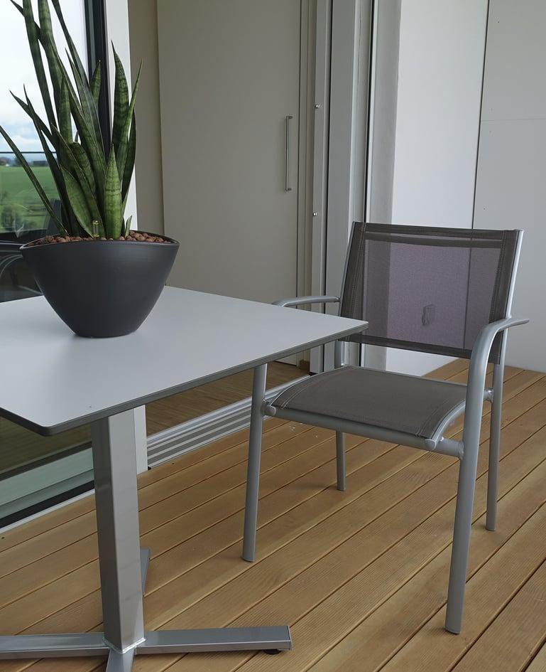 Stuhl aus Stahlrohr mit grauer Bespannung Stahlrohr auf Balkon