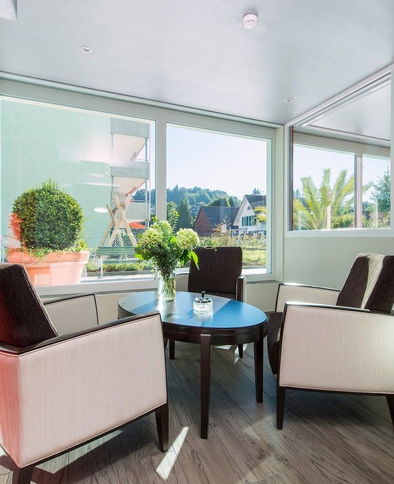 Sitzgruppe mit drei Sesseln und passendem Tisch vor grosser Fensterfront