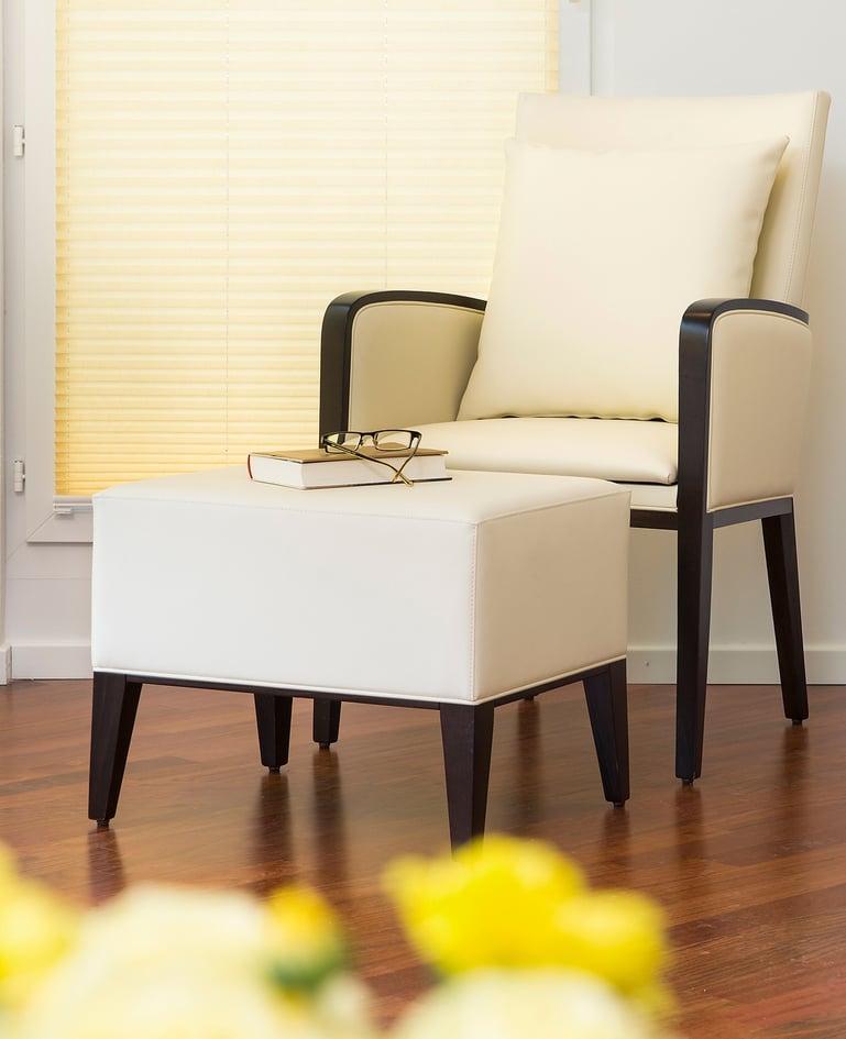 Leseecke mit hellem Sessel und passendem Hocker. Darauf liegen ein Buch und eine Brille.