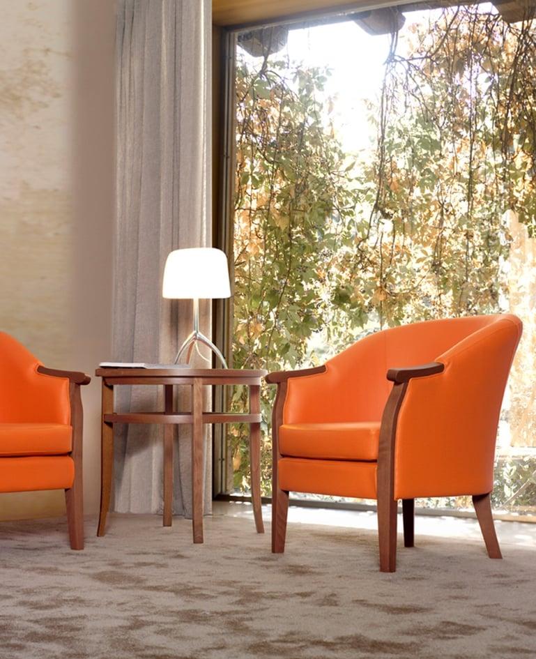 Zwei Sessel mit knalligem, orangem Bezug und passendem Tisch vor einer grossen Fensterfront mit Blick in die Natur