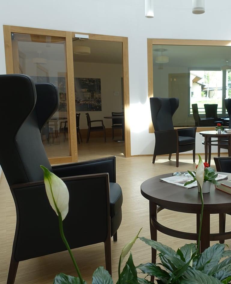 Aufenthaltsraum mit schwarzen Sesseln mit hoher Rückenlehne und Beistelltischen. Dahinter der Durchgang zum Essbereich mit passender Möblierung