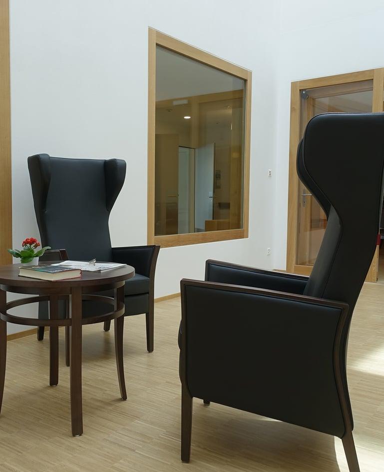 Zwei schwarze, gemütliche Sessel mit Beistelltisch in einem hellen Aufenthaltsraum