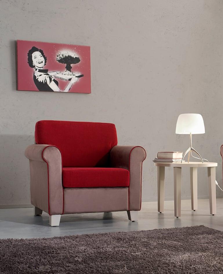 Einzelner gemütlicher, dick gepolsterter roter Sessel mit Beistelltisch, auf dem Bücher liegen