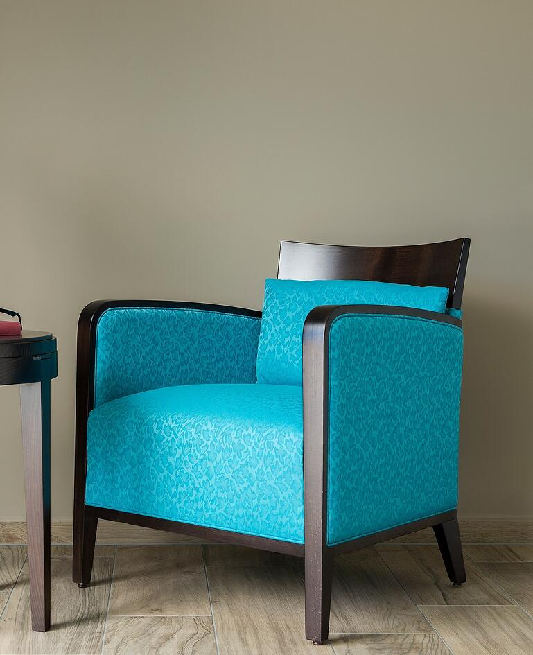 Ausladender Sessel mit türkis gemustertem Bezug und relativ niedriger Rückenlehne