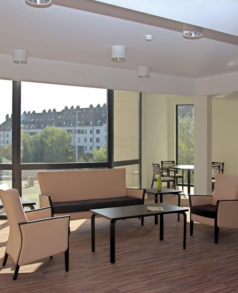 Sofa mit zwei passenden Sesseln um ein Beistelltisch gruppiert, das sich in einem Gemeinschaftsraum mit grosser Fensterfront befindet