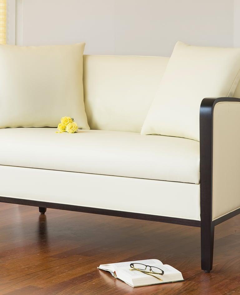 Nahaufnahme von einem hellen, gemütlichen Sofa mit drei gelben Rosen auf dem Sitzpolster. Am Boden liegen ein Buch und eine Brille
