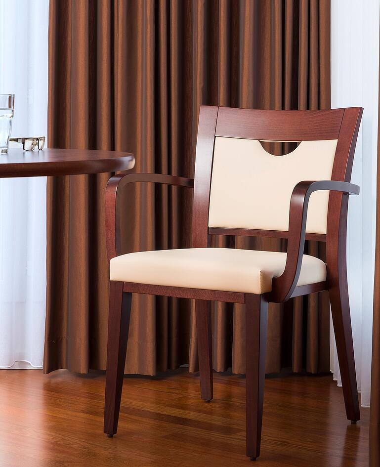 Elegante Holzstuhl mit weissem Polster und halbmondförmiger Aussparung in der Rückenlehne