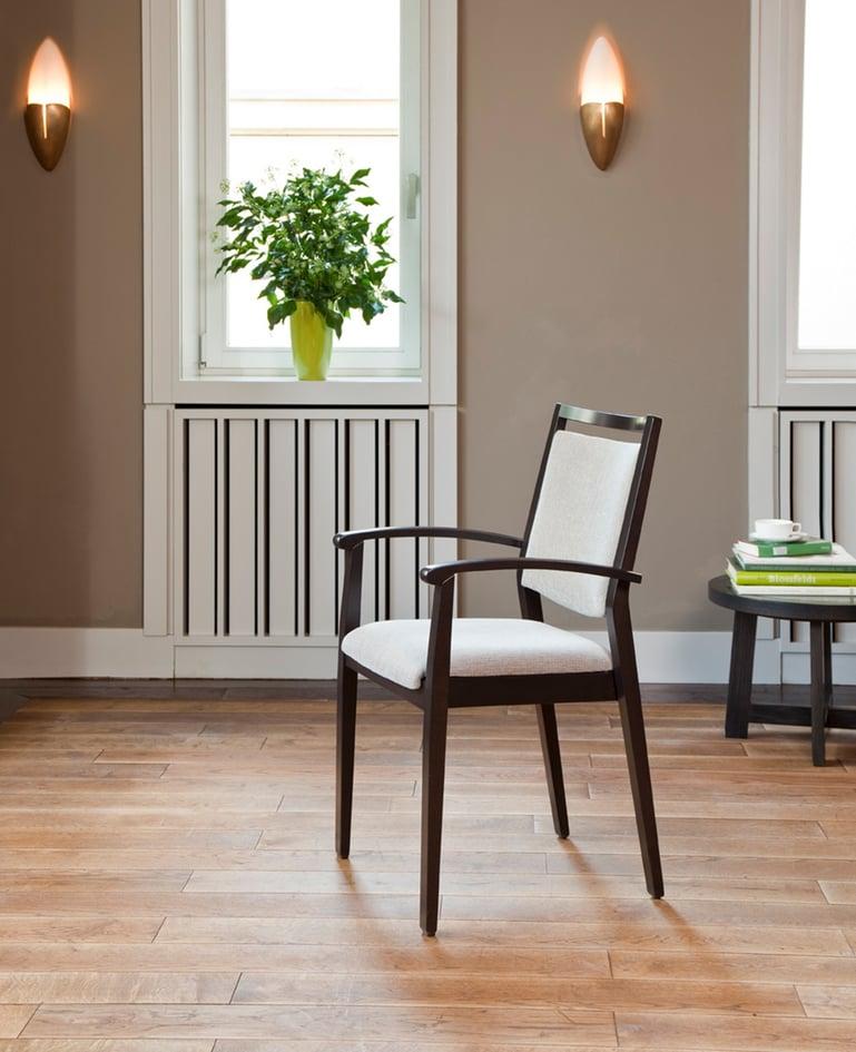 Seitenansicht auf stilvollen Stuhl aus dunklem Holz mit hellem Sitz- und Rückenpolster und Armlehnen