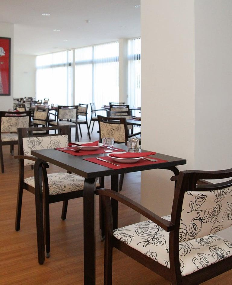 Essbereich mit identischen Stühlen aus dunklem Holz mit hellem Sitz- und Rückenpolster mit Blumenmuster und dazu passende Tische. Der vorderste Tisch ist gedeckt