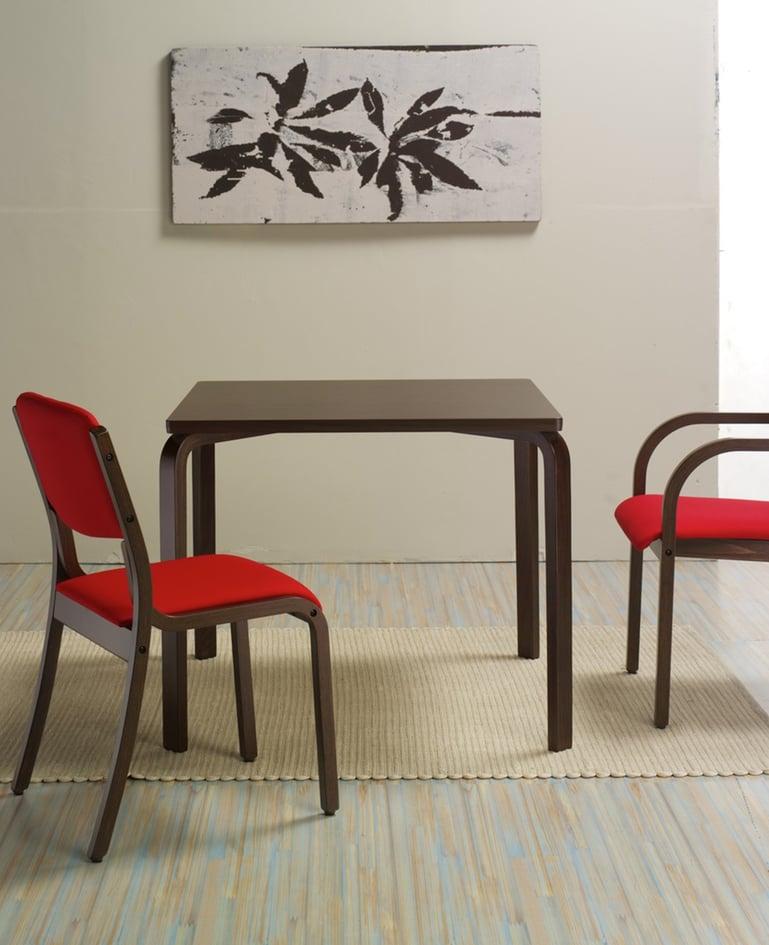 Schlichter Holztisch und zwei passende Holzstühle ohne Armlehne mit roter Polsterung