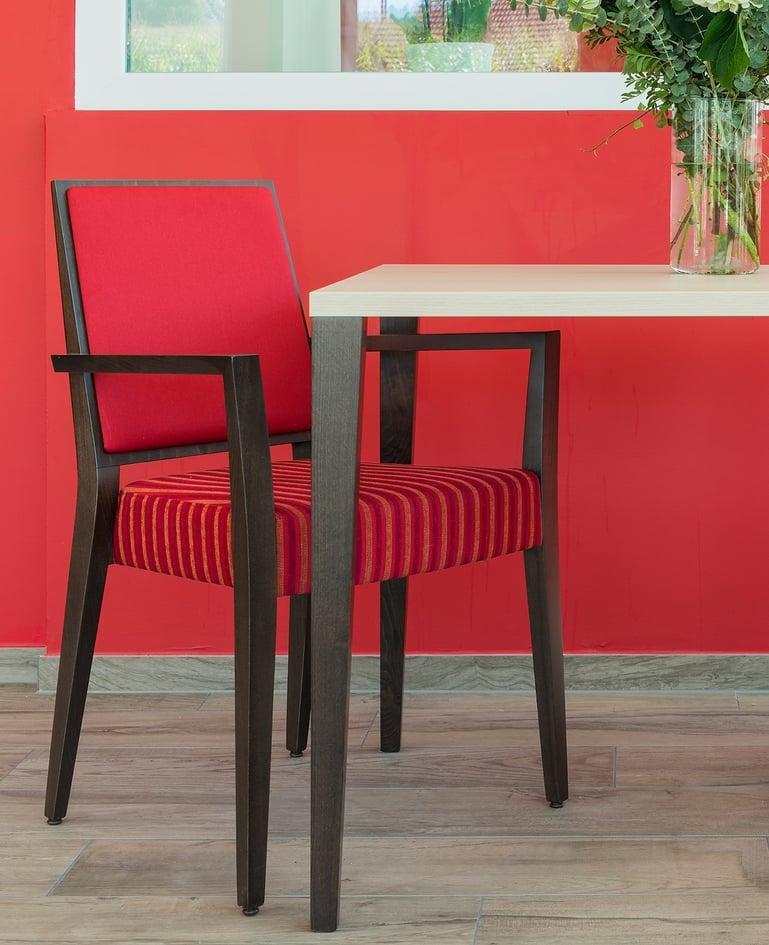 Stuhl aus dunklem Holz mit rotem Rückenpolster und rot gestreiftem Sitzpolster links neben dem passenden Tisch