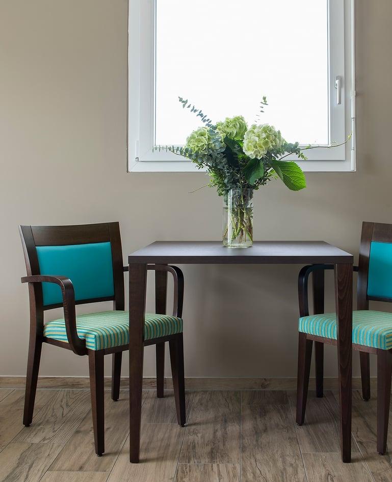 Stühle aus dunklem Holz mit türkisem Rückenpolster, gestreiftem Sitzpolster und Armlehnen. In der Mitte ein passender Tisch mit Blumenstrauss
