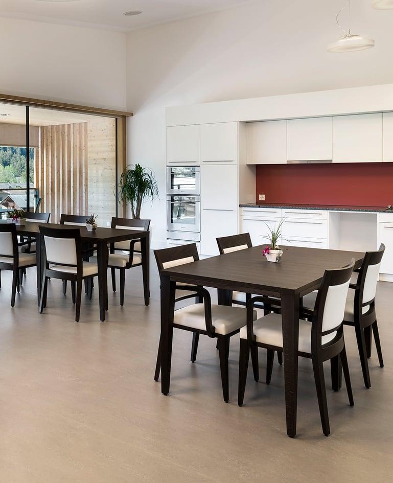 Grosszügiger Essbereich mit Küche, darin befinden sich zwei Tische aus dunklem Holz mit je vier Stühlen mit Rücken- und Sitzpolster sowie Armlehne