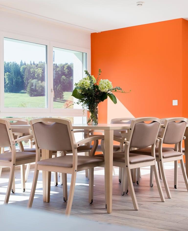 Grosser Tisch mit Blumenstrauss und acht Stühlen mit Rücken- und Sitzpolstern. Das Fenster gewährt Aussicht ins Grüne