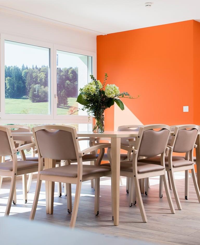 Grosser, heller Tisch mit Blumenvase und acht Stühlen darum gruppiert vor knallig oranger Wand und Fensterfront