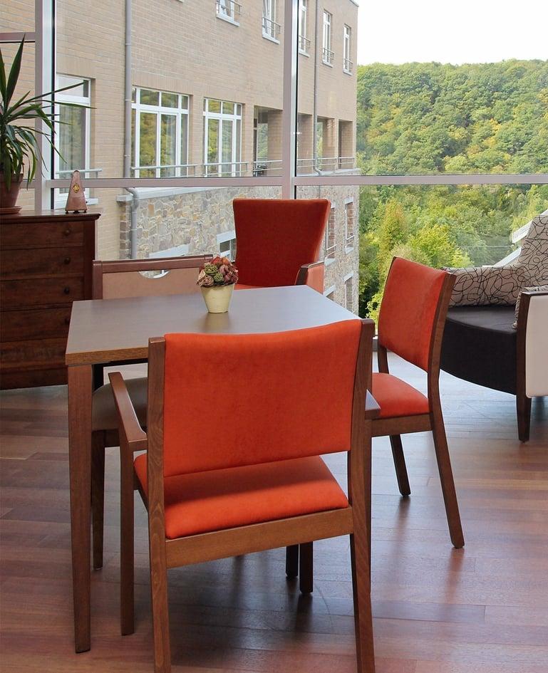 Hölzerner Tisch mit drei passenden, rot gepolsterten Stühlen in einem Aufenthaltsraum mit Aussicht auf Gebäudefassade und ins Grüne
