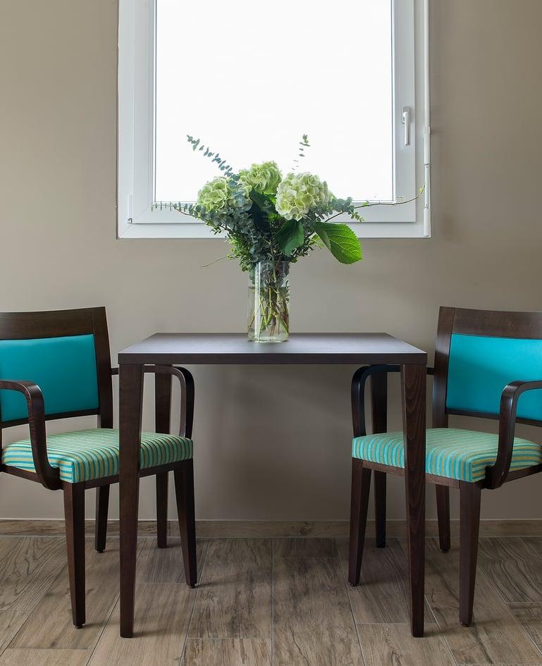 Dunkler Esstisch mit Blumenstrauss in Vase, links und rechts davon zwei gepolsterte Stühle