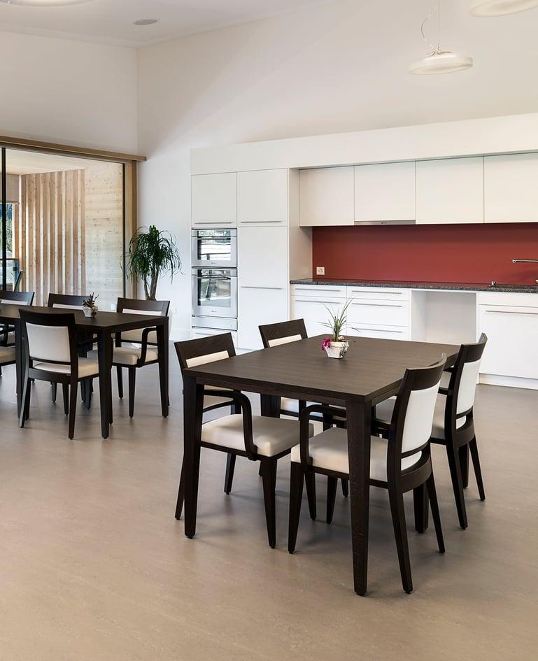 Zwei grosse, dunkle Esstische mit je vier gepolsterten Stühlen in einem Essbereich, der an die Küche angrenzt