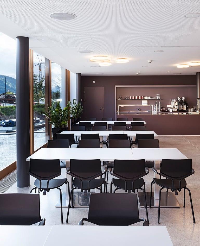 Essbereich in Caféteria mit vier hellen, langen Tischen und jeweils acht Stühlen hintereinander, links davon eine Fensterfront