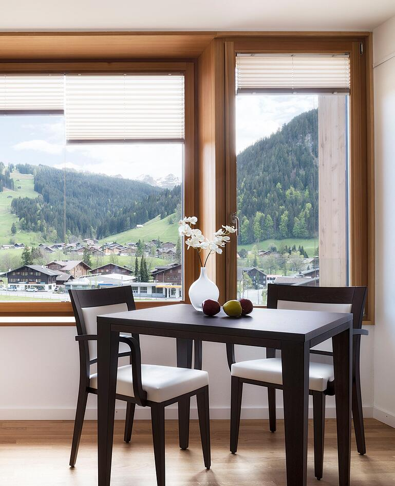 Tisch aus dunklem Holz mit Blumenvase, drei Früchten und zwei passenden Stühlen. Fenster mit Ausblick auf ein Dorf in hügliger Landschaft