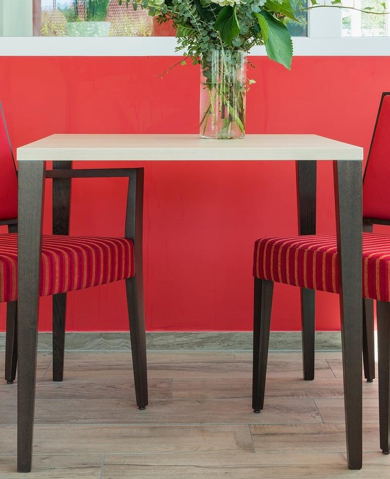 Tisch mit quadratischer Tischplatte und Blumen, links und rechts davon zwei Stühle vor knallig rotem Hintergrund